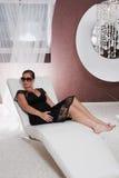 Junge attraktive Frau, die auf Couch aufwirft Stockfotografie