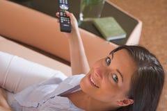 Junge attraktive Frau, die auf Couch sitzt Lizenzfreie Stockfotografie