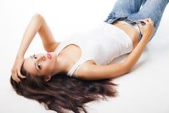 Junge attraktive Frau, die auf dem Studioboden liegt Stockbilder
