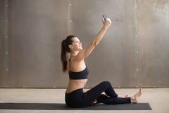 Junge attraktive Frau, die auf der Matte nimmt selfie mit Telefon sitzt Lizenzfreies Stockbild