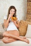 Junge attraktive Frau, die auf Sofa und dem Essen sitzt Stockfoto
