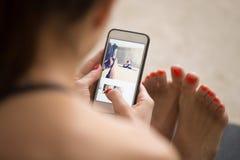 Junge attraktive Frau, die Bilder auf ihr smar sitzt und überprüft Lizenzfreies Stockbild