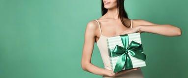 Junge attraktive Frau, die ein Geschenk hat lizenzfreie stockbilder
