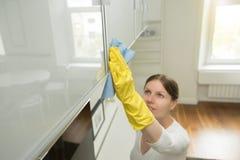 Junge attraktive Frau, die eine Oberfläche von Küche clos säubert Stockfotos
