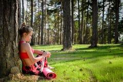 Junge attraktive Frau, die eine Pause nach Yogatraining macht und ihre intelligente Uhr überprüft Stockfotos