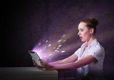 Junge attraktive Frau, die eine Tablette hält Lizenzfreie Stockbilder