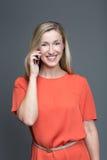 Junge attraktive Frau, die an einem Handy spricht Lizenzfreies Stockbild