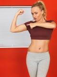 Junge attraktive Frau, die ihre Arm-Muskeln und Zeigen biegt lizenzfreie stockfotos