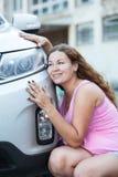 Junge attraktive Frau, die ihren Neuwagen liebt Stockbilder