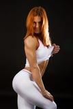 Junge attraktive Frau, die im Gymnastikraum aufwirft Stockfotografie