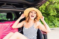 Junge attraktive Frau, die im offenen Stamm eines Autos sitzt Sommer-Autoreise Stockfotografie