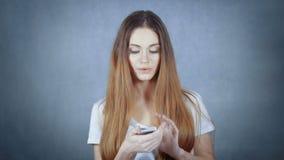Junge attraktive Frau, die intelligentes Telefon über grauem Hintergrund verwendet stock video