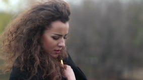 Junge attraktive Frau, die kalt und im Herbstpark einsam sich fühlt stock video