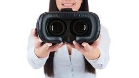Junge attraktive Frau, die Kopfhörer der virtuellen Realität hält Lizenzfreies Stockfoto