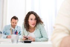 Junge attraktive Frau, die mit Mobile während der Prüfung betrügt lizenzfreies stockbild