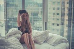 Junge attraktive Frau, die morgens Selbstporträt im Bett macht Stockbild