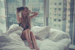 Junge attraktive Frau, die morgens Selbstporträt im Bett macht Stockfotografie