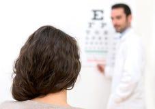 Junge attraktive Frau, die Optikertest durchführt Stockfotografie