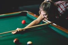 Junge attraktive Frau, die Pool in der Bar spielt lizenzfreie stockbilder