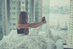 Junge attraktive Frau, die selfie im Bett macht Stockbilder
