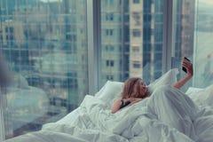 Junge attraktive Frau, die selfie im Bett macht Stockfotografie
