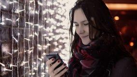 Junge attraktive Frau, die Smartphone im fallenden Schnee nachts die Heilige Nacht steht nahe Lichtwand verwendet, Stockfoto