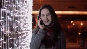Junge attraktive Frau, die am Telefon im fallenden Schnee nachts die Heilige Nacht steht nahe Lichtwand spricht, Lizenzfreies Stockfoto