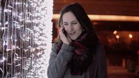 Junge attraktive Frau, die am Telefon im fallenden Schnee nachts die Heilige Nacht steht nahe Lichtwand spricht, Stockfotografie