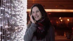 Junge attraktive Frau, die am Telefon im fallenden Schnee nachts die Heilige Nacht steht nahe Lichtwand spricht, Stockfoto