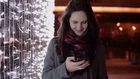 Junge attraktive Frau, die am Telefon im fallenden Schnee nachts die Heilige Nacht steht nahe Lichtwand spricht, Lizenzfreie Stockfotos