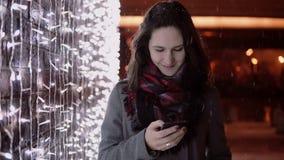 Junge attraktive Frau, die am Telefon im fallenden Schnee nachts die Heilige Nacht steht nahe Lichtwand spricht, lizenzfreie stockbilder
