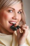Junge attraktive Frau, die Traube isst stockfotos