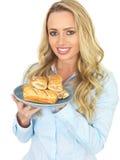 Junge attraktive Frau, die voll eine Platte von frisch gebackenem Saugage Rolls hält und isst Stockfoto