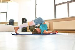 Junge attraktive Frau, die Yoga im Eignungsraum tut Nat?rliches Licht umgebend stockbilder