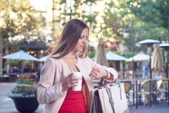 Junge attraktive Frau, die Zeit auf Armbanduhr überprüft lizenzfreie stockbilder