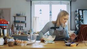 Junge attraktive Frau, die zu Hause in der Küche kocht Schöne Hausfrau, welche die Mahlzeit, unter Verwendung der Küchenskalen vo stock footage