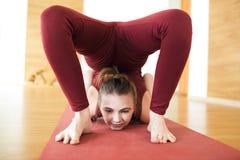 Junge attraktive Frau in einem übenden Yoga des roten Anzugs, stehend in der Skorpionsübung, vrischikasana Haltung und arbeiten,  lizenzfreie stockfotografie