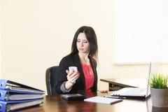 Junge attraktive Frau in einem Anzug betrachtet den Schirm des Smartphone auf den Schreibtisch im Büro Stockfotografie