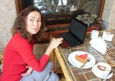 Junge attraktive Frau in einem Kaffee mit einem Laptop Stockbild