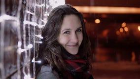Junge attraktive Frau im fallenden Schnee nachts die Heilige Nacht, welche die Kamera steht nahe Lichtwand betrachtet, Lizenzfreie Stockbilder