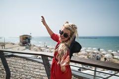 Junge attraktive Frau im hellen roten Kleid tanzt auf die Stadtpromenade Lizenzfreie Stockbilder