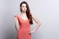 Junge attraktive Frau im korallenroten Kleid Stockbild