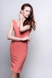 Junge attraktive Frau im korallenroten Kleid Stockbilder