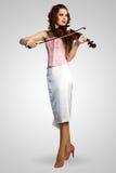 Junge attraktive Frau im rosa Korsett auf einer Violine Lizenzfreies Stockfoto