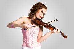 Junge attraktive Frau im rosa Korsett auf einer Violine Stockfotografie