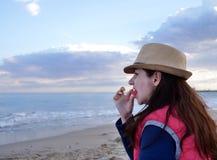 Junge attraktive Frau isst Wassermelone auf dem Strand nahe dem Meer stockfoto
