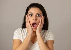 Junge attraktive Frau mit einem überraschten und entsetzten Gesicht, Augen und einem Mund weit offen lizenzfreie stockbilder