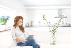 Junge attraktive Frau mit einer Tablette im modernen Innenraum lizenzfreie stockbilder