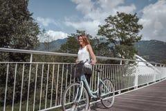 Junge attraktive Frau mit Fahrrad auf einer Br?cke lizenzfreies stockfoto