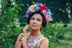 Junge attraktive Frau mit Krone von Blumen Lizenzfreie Stockfotografie